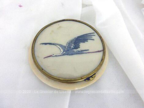 Ancien poudrier rond en bakélite avec miroir et encore un peu de poudre maintenue par un film treillis et au couvercle décoré d'un dessin de cigogne.