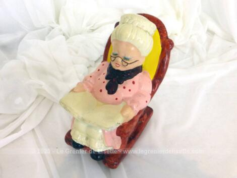 Voici une tirelire en céramique avec une grand-mère en train de lire sur son rocking chair.