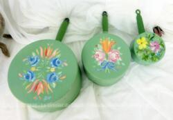 """Trio de casseroles de différentes tailles décorées à la main sur fond vert pastel et des dessins uniques de fleurs colorées avec la signature """"LeRoy"""" sur le dessous"""