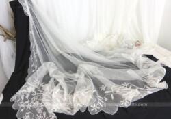 Superbe voile de mariée ancien en tulle ivoire brodé de volutes et de fleurs en forme de demie-lune sur 240 cm de large sur 130 cm de haut. Pour une décoration trop vintage.