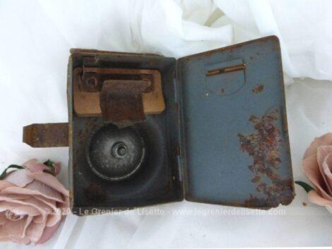 Datant des années 50, voici une ancienne lampe de poche en tôle patinée par les marques d'oxydation avec sur l'avant un bouton poussoir et un verre loupe et bombé pour protéger l'ampoule.