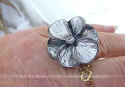 Montée sur métal couleur argent, voici une belle bague en forme de fleur aux pétales ouverts et dont l'anneau en perles métalliques est étirable. Idéal pour tous les doigts à partir de 2 cm de diamètre.