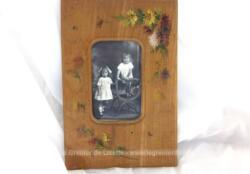 Voici un cadre ancien décoré de bouquets de fleurs peints à la main de avec une photo du début du siècle dernier représentant deux petits filles. Pièce unique.