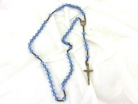 Voici un ancien chapelet aux perles de verre à facettes bleu ciel avec croix et médaille en métal argenté.