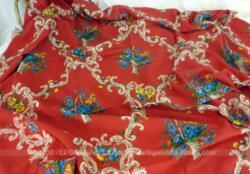 Coupon de tissus d'habillement en polyester avec dessins de fleurs et volutes sur fond rouge de 140 x 110 cm.