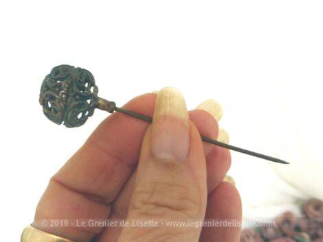 Ancienne petite épingle à chapeaux de 8 cm est composée d'une partie sphérique métallique ciselée par des volutes et arabesques pour la décorer comme un bijoux.