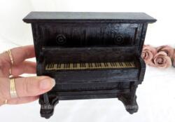 Voici un ancien piano droit en bois pour maison de poupées fait main et daté de 1932 avec son couvercle qui se soulève pour laisser apparaitre un papier représentant le clavier.
