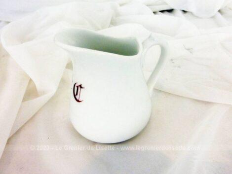 Voici un petit pot à lait en faïence blanche, numéroté et décoré en bordeaux de deux monogrammes, E et C ?