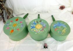 """Trio de casseroles de différentes tailles décorées à la main sur fond vert pastel et des dessins uniques de fleurs colorées avec la signature """"LeRoy"""" sur le dessous."""
