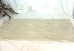 Ancien napperon au crochet fil coton bistre, de 110 x 38 cm avec un motif de quadrillage de volutes et de fleurs au centre.