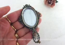 Sur 8.5 cm de long, voici un adorable et original petit miroir face à main décoré de belles volutes et décorations en métal sur le pourtour et le manche.