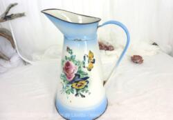 Ancien broc émaillé sur fond bleu avec décorations fleuries d'origine et sa patine authentique avec éclats et traces d'oxydation.