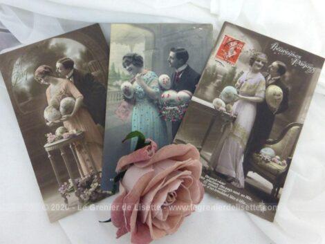 """Voici un lot de 3 cartes postales anciennes de couples qui souhaitent """"Heureuses Pâques"""" avec de gros oeufs dans les bras sur des photos colorisées."""