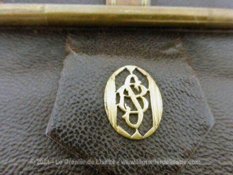 Voici une sacoche minaudière vintage en cuir marron à porter à la main avec monogrammes sur le fermoir.