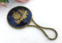 Adorable miroir face à main avec en décoration une scène galante dorée sur fond bleu marine.