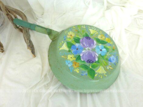 Ancienne poêle décorée à la main sur fond vert pastel avec des dessins uniques de fleurs colorées. Pour une décoration vintage.
