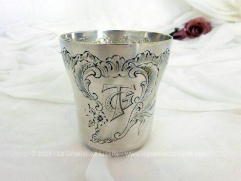 Voici un ancienne timbale de baptême en métal argenté gravés des monogrammes GT dans un grand écusson avec une frise de dessins de fleurs et de feuilles.