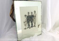 Sur 24 x 18 cm, voici un ancien cadre miroir des années 40 avec une vieille photo de 12 x 17 cm datant des années 20 avec tous les enfants d'une même famille.