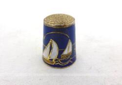 Voici un dé en laiton émaillé sur fond bleu avec les dessins de 4 voiliers voguant sur l'eau autour d'un phare.