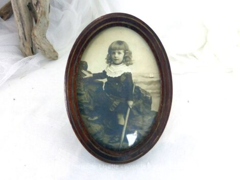 Voici un ancien petit cadre ovale de 13 x 10 cm en bois de loupe avec une photo du début des années 1900 d'un garçonnet aux longues boucles .