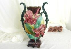 Voici un ancien vase en barbotine aux grandes fleurs d'iris rose en relief. Ses anses, son col et son socle en soulignent toute son harmonie.