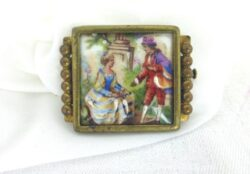 Superbe et originale voici une ancienne broche en laiton sertissant un écusson en porcelaine Limoges représentant une scène galante façon Fragonard.