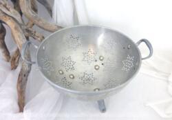 Sur 20.5 cm de diamètre, voici une ancienne passoire tripode en aluminium avec des trous pour égoutter en forme d'étoile.