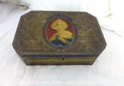 Voici un ancienne boite en métal avec sur le couvercle un écusson avec le dessin d'une femme des années 20 en sérigraphie