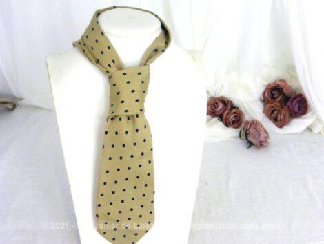 Voici une ancienne cravate en soie sur fond beige et décorée de pois couleur marine. Pour homme ou femme !