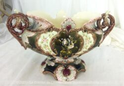 Façon barbotine, voici une superbe jardinière en porcelaine émaillée et numérotée sur fond vert empire et blanc irisé et décorée d'écussons grenat et fleurs roses.