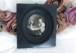 En bois noirci, voici un ancien petit cadre carré (presque 10 x 11 cm) ouvragé pour laisser la place à une photo ronde représentant un garçonnet. Pièce unique.