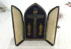 Voici un ancien autel reliquaire de voyage en cuir avec à l'intérieur une croix en bois portant un Christ en métal et à ses pieds deux statuettes .