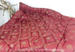 Voici un ancien édredon bien épais de 122 x 122 cm en tissus bordeaux satiné rembourré par de la laine cardée maintenues par des coutures piqués formant un quadrillage trés esthétique.