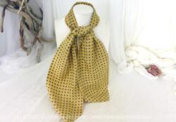 Voici un ancien foulard modèle Ascot en soie sur fond de couleur paille et décorée de pois sur 128 cm de long et 18 cm de large aux extrémités.