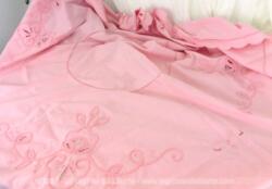 Ancienne nappe ronde de 148 cm de diamètre en coton teinté en rose pastelc décorée de belles broderies et de jours pour former des dessins.