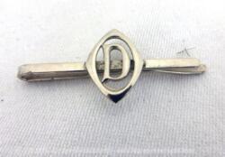 Voici une ancienne pince à cravate des années 60/70 avec en décoration le monogramme D. Alors pour cravate pour homme ou pour foulard pour femme ?