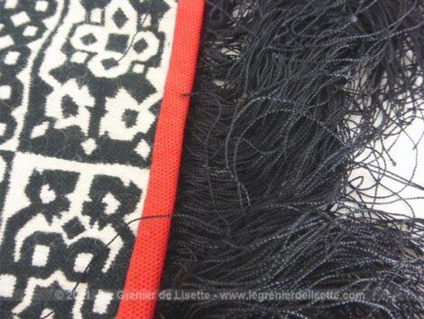 Voici un châle, tout en motif quadrillé noir et blanc, avec un beau liseré rouge sur la bordure et de longues franges noires.