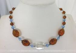 Ancien collier réalisé avec des perles de verre couleur ambre en taille croissante , entremêlées par des petites perles à facette et une grande perle translucide au centre.