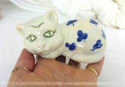 Voici une belle petite figurine représente un chat blanc aux grands yeux verts avec des feuilles bleues sur le corps et signé Vallauris.