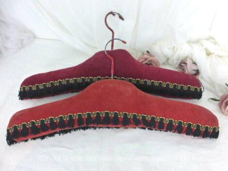 Voici un duo de cintres en velours deux tons de rouge différents et décorés de d'un galon frangé noir.